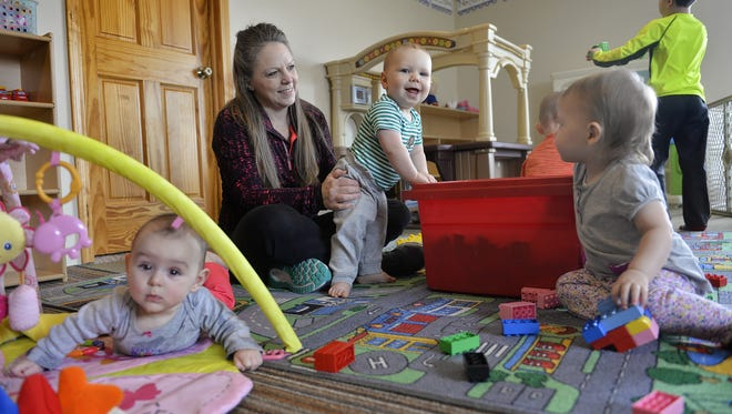 In this file photo from 2016, child care provider Kelly Martini holds Abel Sand as she plays with some of her charges  at her Avon-area home.