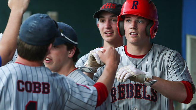 At right, Roncalli Rebel Nick Schnell (7) is congratulated by teammates after an RBI double led him to score the team's first run of the game in the bottom of the first inning of the Marion County tournament final at Victory Field in Indianapolis, Monday, May 14, 2018. Roncalli won the Marion County title, 5-3.