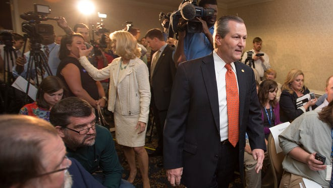 Alabama House Speaker Mike Hubbard walks into a press conference on Tuesday, Oct. 21, 2014, in Auburn, Ala. Speaker Mike Hubbard was accused of 23 felony counts of using his office for private gain.