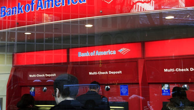 In this Jan. 31, 2011 photo, Bank of America customers use ATM machines in New York.  (AP Photo/Mark Lennihan)