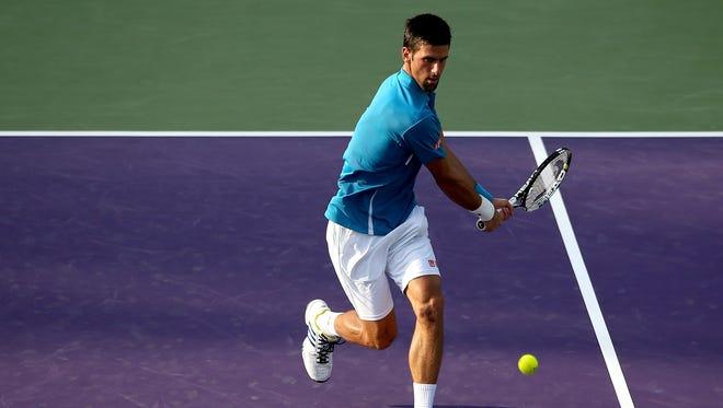 Novak Djokovic of Serbia returns a shot to Joao Sousa of Portugal during the Miami Open.