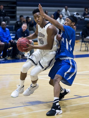 Timber Creek senior guard Randy Bell goes around Keenan Wise of Paul VI during action earlier this season.