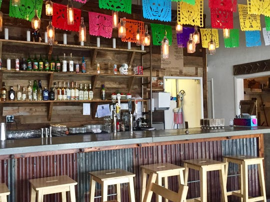 The dining room and bar at the new Midtown Tacos are strung with colorful Day of the Dead pennants.