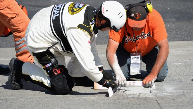 Workers patch a hole in the track at Dover International Speedway going into Turn  during Sunday's FedEx 400 Benefiting Autism Speaks.
