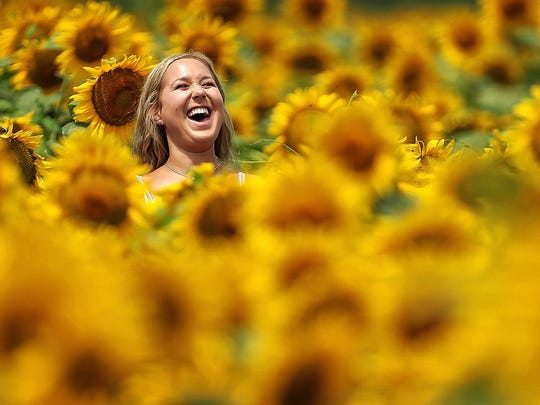 Allison Carr, 18, jokes with her friends while walking through the sunflowers at the Shelby Farms Agricenter.