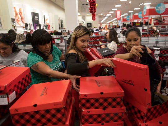 Women look through boxes of boots in JCPenney shortly