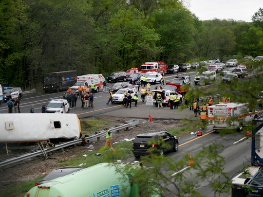 Emergency personnel work at the scene of a school bus and dump truck collision, injuring multiple people, on Interstate 80 in Mount Olive, N.J., Thursday, May 17, 2018. (Ed Murray/NJ Advance Media via AP)