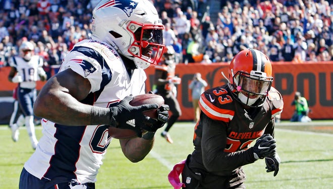New England Patriots tight end Martellus Bennett runs past Cleveland Browns free safety Jordan Poyer (33) for a long touchdown reception Sunday, Oct. 9, 2016, in Cleveland.