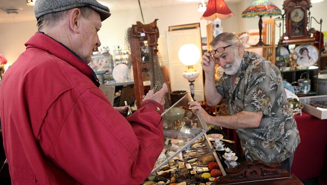 Sandy Feddima (left) of Bridgeton examines a small oil tin used to lubricate a sewing machine with vendor Tom Hubler of Laurel, Del., during last year's Mid-Winter Antiques Show at Wheaton Arts and Cultural Center in Millville.