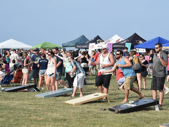 Beer-drinkers play cornhole at Brews By the Bay, which returns to the beach this weekend.