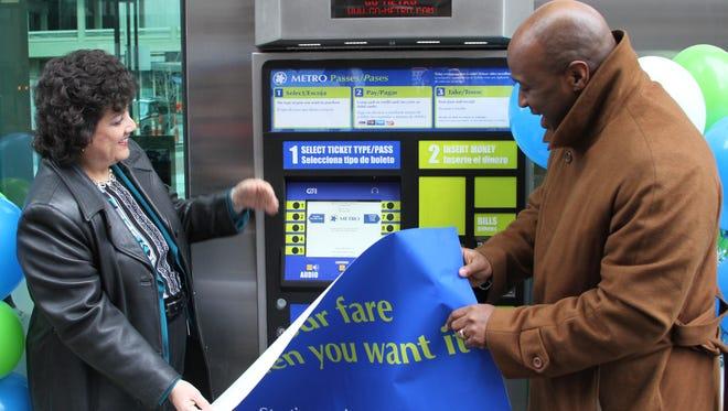 Metro officials Terry Garcia Crews, left, and Jason Dunn unveil the first transit ticket vending machine in Cincinnati.