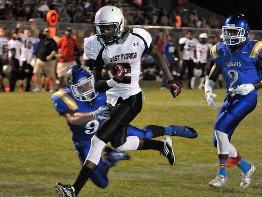 Damond Johnson, No. 2 on the West Florida High roster, sheds Washington High defenders on his way to the end zone during the Washington High Wildcats spring half-game against the West Florida Jaguars at WHS Friday night.