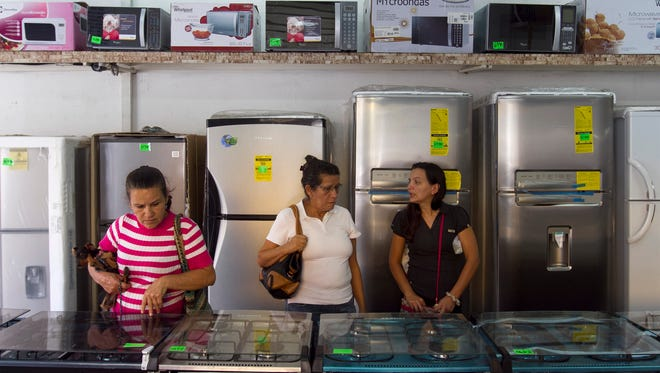 Shoppers look at stoves at an appliance store that has slashed prices in Caracas on Nov. 15.