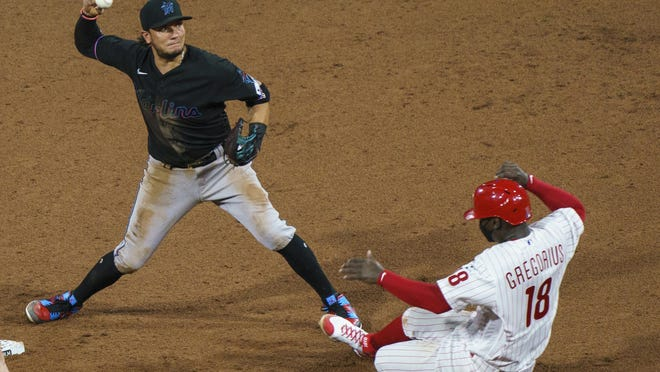 Marlins shortstop Miguel Rojas, left, turns the double play after forcing out the Phillies' Didi Gregorius at second base during Miami's 5-2 season-opening win Friday night at Citizens Bank Park.