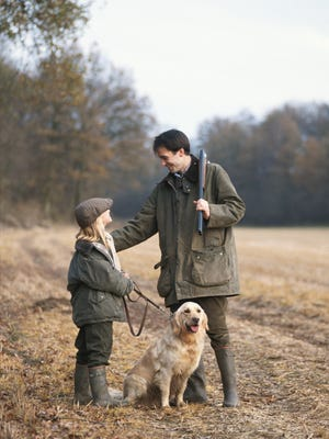 Father and daughter with dog standing in forest