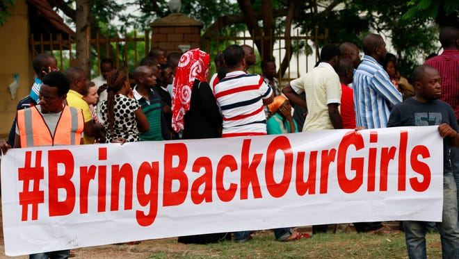 People attend a rally calling on the Government to rescue the school girls kidnapped from the Chibok Government secondary school, in Abuja, Nigeria, Saturday May 10, 2014.