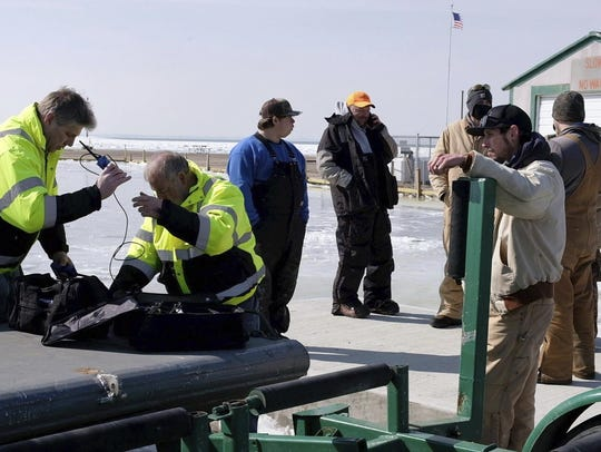 Fisherman James Gibelyou, left, watches a rescue crew
