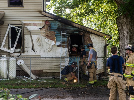 Firefighters work at the side of the residence at 10 Fleshman Mill Rd in Oxford Township on Sunday.