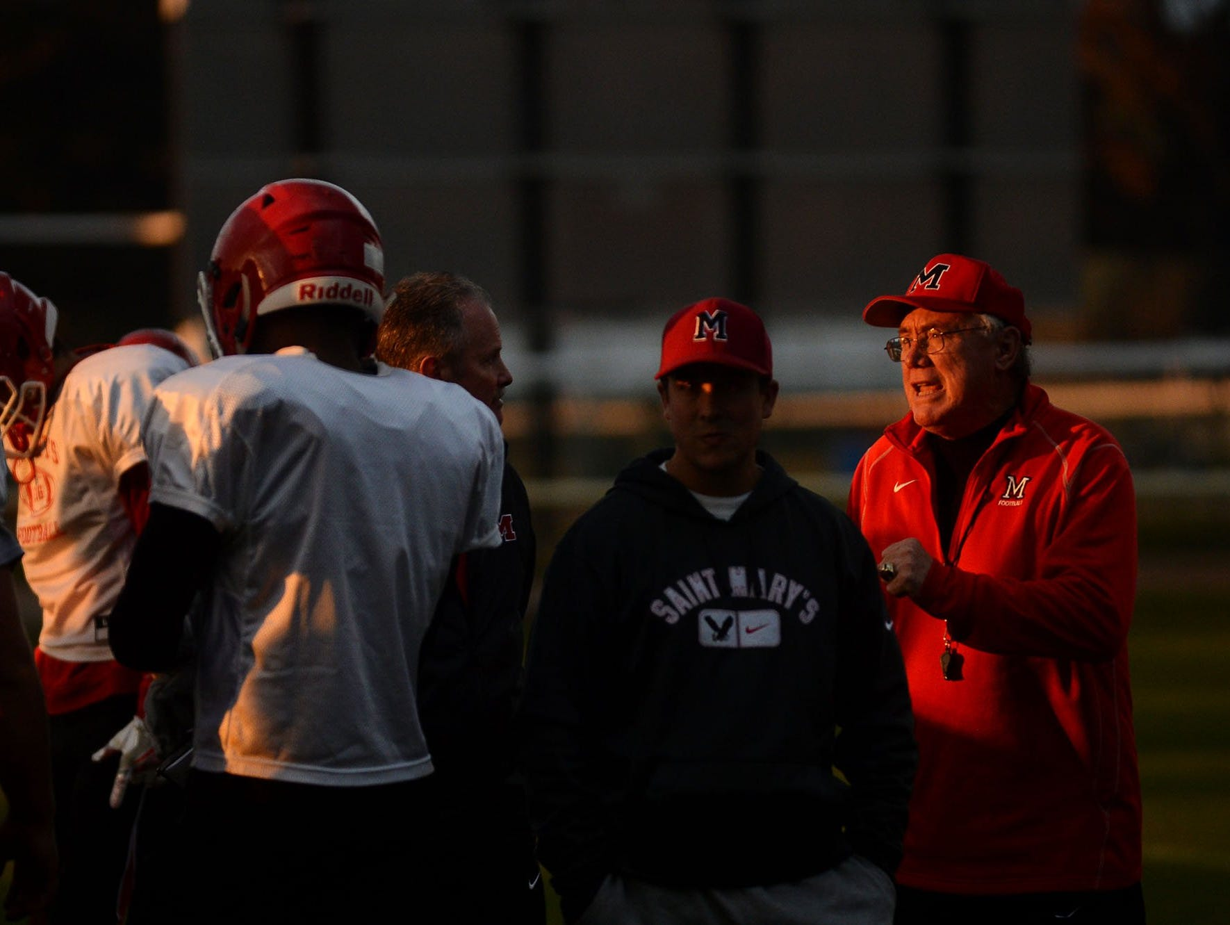 Orchard Lake St. Mary's football head coach George Porritt, right, talks to players and fellow coaches during practice on Tuesday, Nov. 8, 2016 at Orchard Lake St. Mary's.