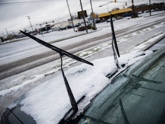 A car's windshield wipers are lifted up to protect