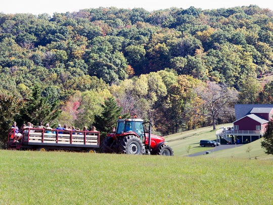 People roll along York Township hills changing for the season during a hay ride at the Wyndridge Farm Fall Festival in York Township.