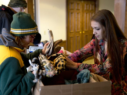 Nina Weiland, left, gets help Thursday from volunteer Deyani Boelter in finding a warm pair of gloves during the Fox Cities Housing Coalition's resource fair at Riverview Gardens in Appleton.