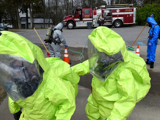 West Wilson Utility employees walk back to the staging area after being decontaminated by members of WEMA during a HazMat training exercise that simulated a chlorine leak at West Wilson Utility's water treatment plant on Beth Dr