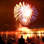 People line the shore of Sheldon Lake in Fort Collins as Independence Day fireworks explode over the water in this 2012 file photo.