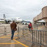 Frontier Airlines passengers head out to the tarmac to board their flight to Chicago at Trenton-Mercer Airport on April 18, 2013. Frontier began flying out of Trenton, New Jersey, in November 2013 and out of New Castle Airport in July 2013.