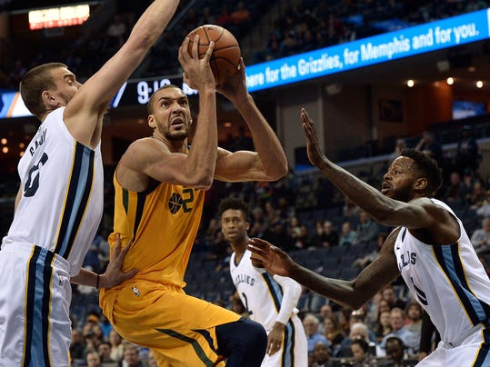 Utah Jazz center Rudy Gobert (27) drives between Memphis Grizzlies center Marc Gasol, left, and forward JaMychal Green, right, in the first half of an NBA basketball game Friday, March 9, 2018, in Memphis, Tenn. (AP Photo/Brandon Dill)