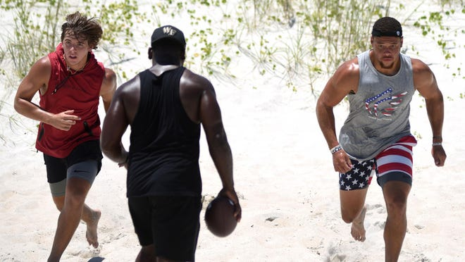 Ashley High School alumnus and current Pittsburgh Steeler Alex Highsmith (right) and trainer Tarence Williams (center) have been joined at workouts for the past three months by West Brunswick rising junior linebacker Carter Wyatt (left). Their final local session together came Friday at Carolina Beach.