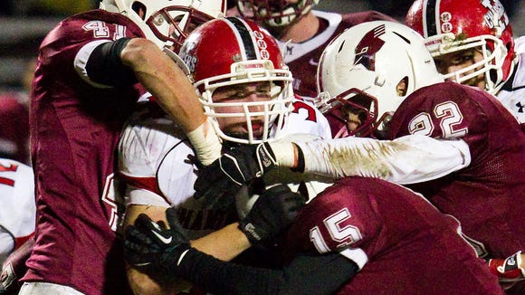 Middleton players swarm Sussex Hamilton running back Drew Patterson in the 2012 playoffs.