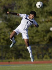 World of Inquiry's Yusuf Jeylani jumps to win a header.