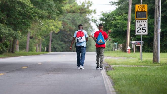 Malik Griggs, 17, left, and Trae Calhoun, 14, walk home from Booker T. Washington High School on East Burgess Road in Pensacola on Thursday, Aug. 10, 2017.  Because there are no sidewalks on East Burgess Road between North Davis Highway and Sanders Street, students often walk in the road, especially on rainy days like when the roadsides are muddy.