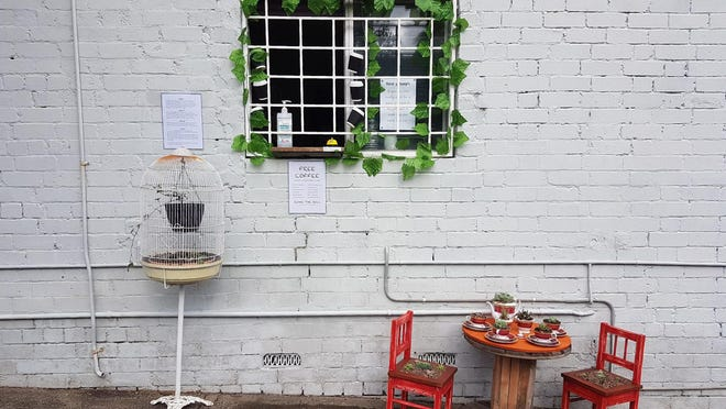 A small table decorated with succulents sits in July below a window where Rick Everett offers free coffee and conversation to friends and neighbors at his home in Sydney, Australia, during the coronavirus pandemic.