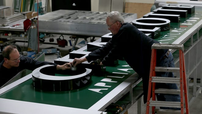 Eric Schaetzke and Steve Betts work Monday on the new Charlotte Appliance sign at Premier Sign Systems.