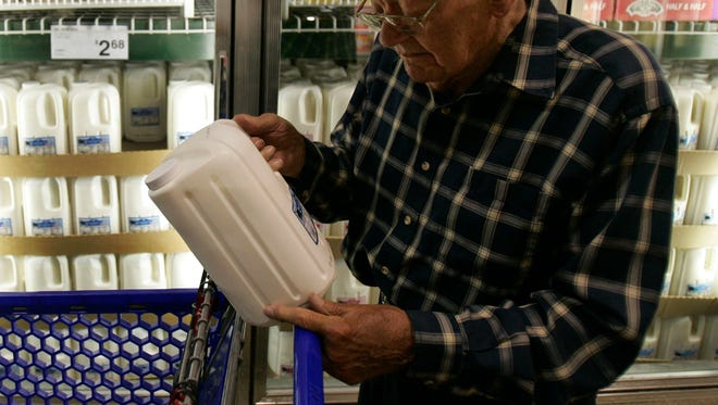 John Ponn, 85, looks at the expiration date on milk contained in a newly designed jug at a Sam's Club, Wednesday, July 2, 2008, in Willoughby Hills, Ohio. (AP Photo/Tony Dejak)