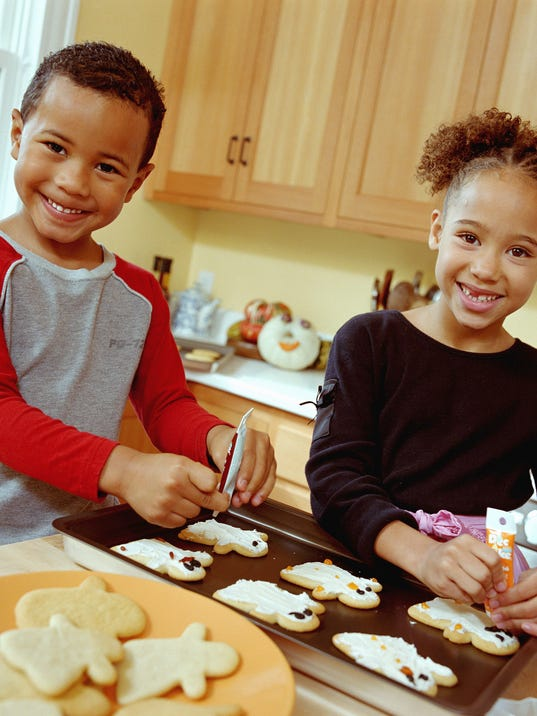 Boy (4-6) and girl (6-8) icing gingerbread men, smiling, portrait