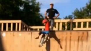 Screenshot of Marcus Crossland pushing his stepson down a skate ramp.