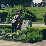 Col. Deborah Campbell lays a wreath of purple and yellow flowers on an engraved memorial stone in front of State Police Troop K's headquarters during the annual Memorial Day ceremony Friday. Campbell will retire this weekend after 30 years of service with state police.