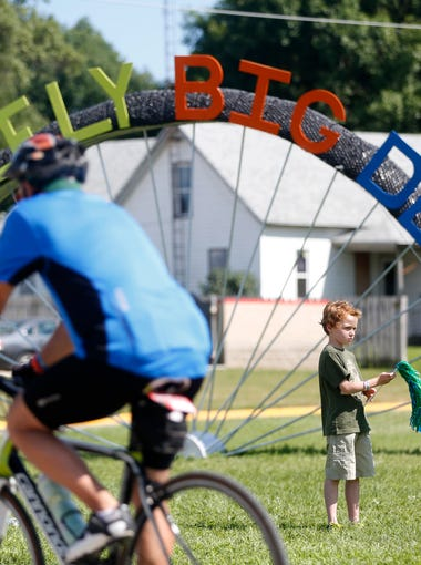 Lane McIntyre, 8, of St. Joseph, Minn., waves at incoming cyclists Tuesday, July 21, 2015 in as RAGBRAI riders make their way into stop over town of Eldora, Iowa. McIntyre was in town visiting his grandparents, who live in Eldora.
