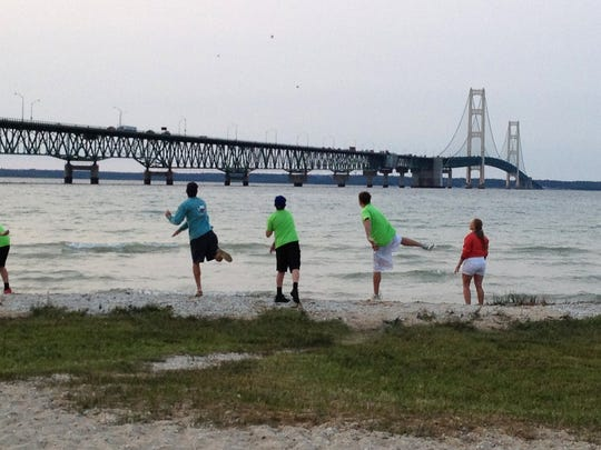 Boys all throw stones into Lake Huron on a cool July