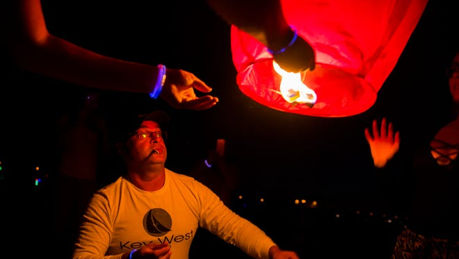 Brian Lampkin and his family, from Ontario, light a lantern on the beach before the fireworks during the New Year's Eve celebration at Naples Pier on Saturday, Dec. 31, 2016, in downtown Naples.