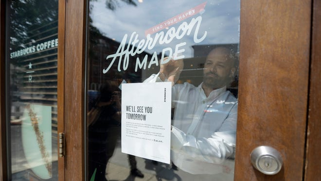 A man tapes a sign to a door at a Starbucks Coffee shop, Tuesday, May 29, 2018, in Philadelphia.