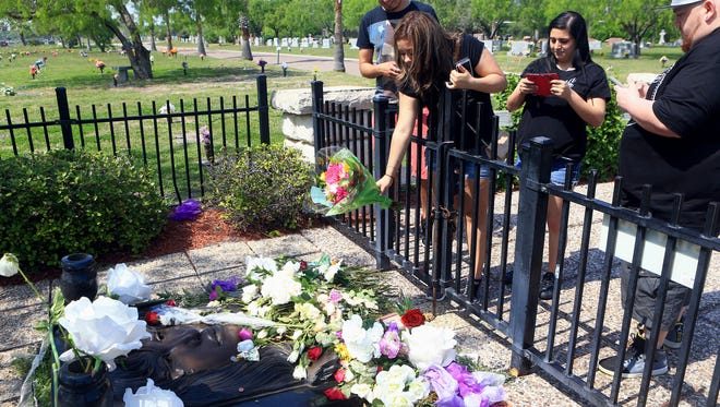 Mariela Garcia from Ft. Worth tosses a bouquet of roses as she pays respect to Selena Quintanilla Perez gravesite on the second day of Fiesta de la Flor on Saturday, March 25, 2017, at Seaside Memorial Park.