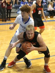 Lucas' Jackson Hauger secures the basketball in front of St. Peter's Luke Henrich in Friday's game.