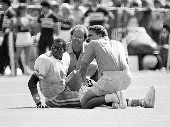 Tennessee trainer Tim Kerin, center, and a staff member take a look at Tony Robinson (10) after the quarterback was injured on the first play of the last quarter against Alabama on  Oct. 19, 1985.