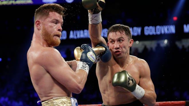 Gennady Golovkin, right, throws a right at Canelo Alvarez during a middleweight boxing bout Saturday, Sept. 16, 2017, in Las Vegas. (AP Photo/John Locher) ORG XMIT: NVJL134