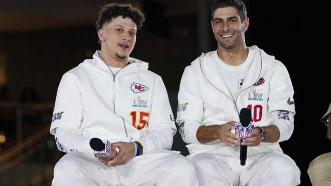 The Chiefs' Patrick Mahomes, right, chats with the49ers' Jimmy Garoppolo during Opening Night for Super Bowl 54 on Monday at Marlins Park in Miami.