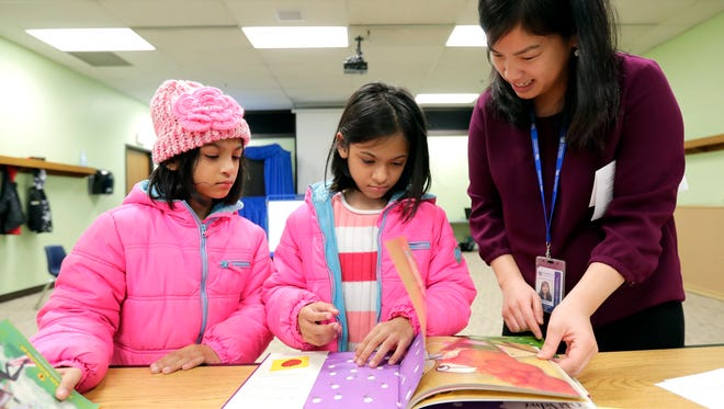 Esther and Ruth Barraza pick out books with Pa Ja Yang during the English Language Learners program at the Appleton Public Library in 2016. File photo.